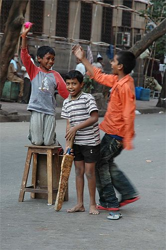 "What a piece of Willow!! It'll do anyway!  Catherine Edwards: ""Kids playing cricket in the middle of the road in Mumbai, January. Although they didn't have either a pitch or a set of stumps, they still had a very tense and exciting match!"" What an excellent 'blade' and what smiles!"