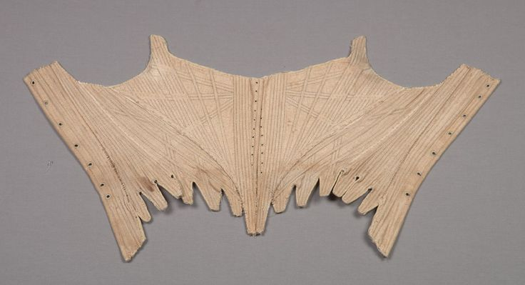 Corset (ca. 1775-1790) of light brown linen; partial straps at shoulder; eyelets along center front and back for lacing; shaped with vertical, horizontal, and diagonal seamed channels; wooden busks at center front; tabbed hem.