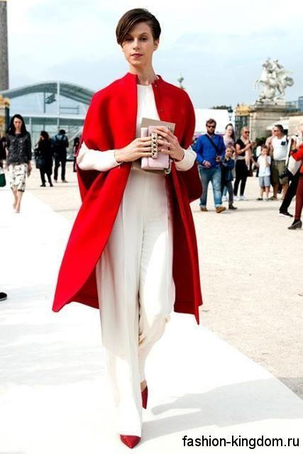 Осеннее пальто-кейп красного цвета, длиной до колен в сочетании с белой кофточкой и широкими брюками белого тона.