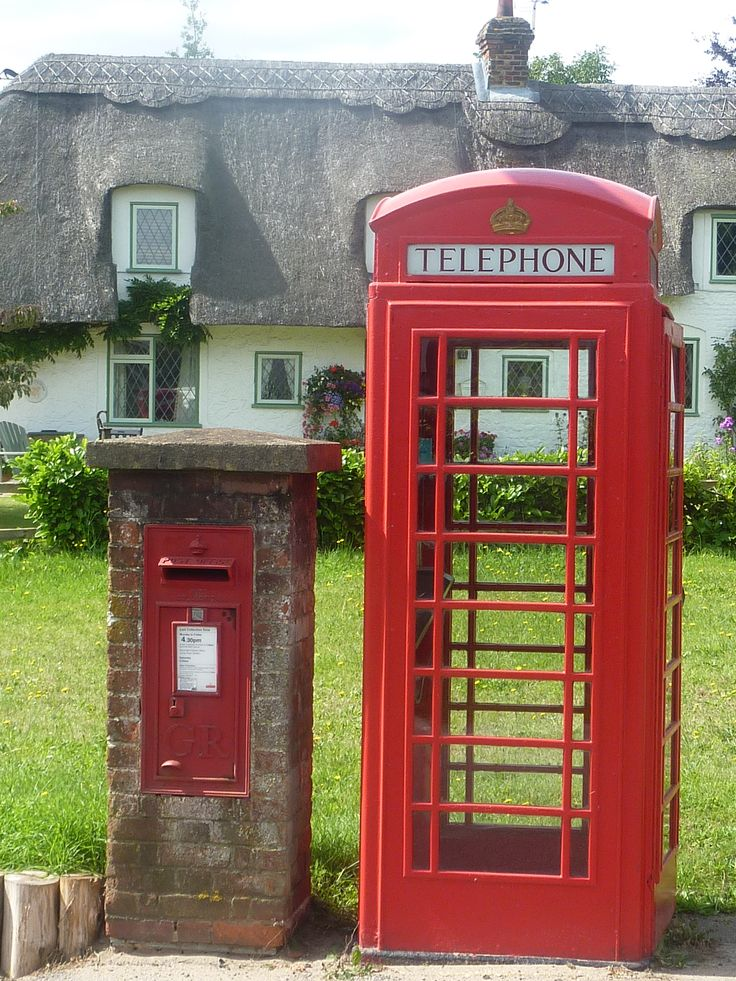 Thatched cottage behind a red phone box and letter box.