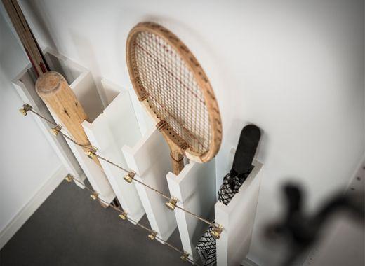 Een IKEA MOSSLANDA oplossing met schilderijenplanken die verticaal aan de wand zijn gemonteerd om tennisrackets, honkbalknuppels en paraplu's rechtop op te bergen.