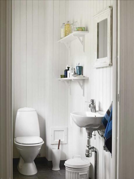Toaletten går i samma somriga ton som övriga huset. Två enkla konsolhyllor räcker för behoven. Handd...