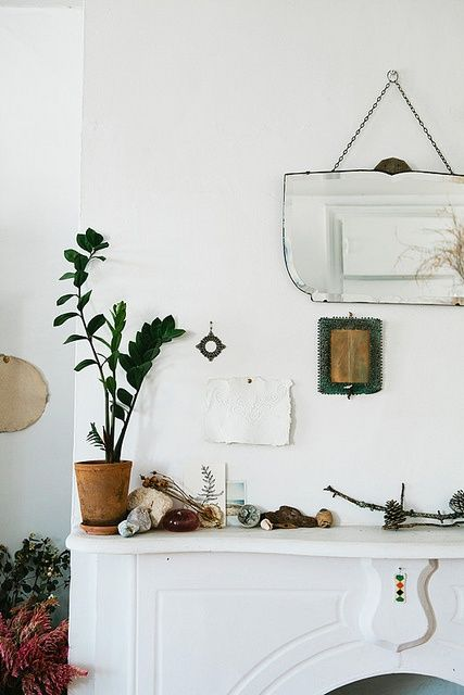 I like the mix of green, white, and brown in this room, all of the little treasures on the mantlepiece, and the unique mirror.