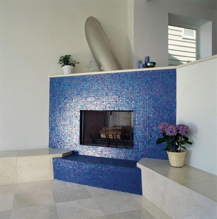 Oceanside Glass Blue iridescent glass mosaic surrounds fireplace