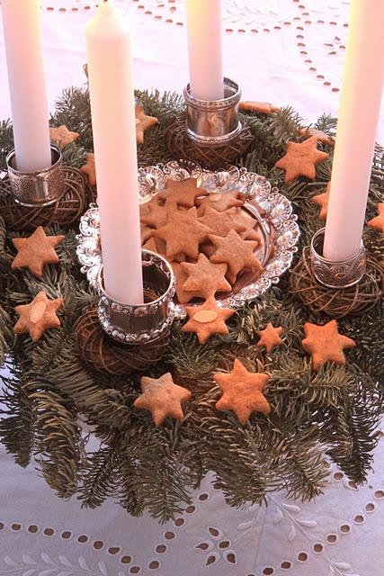 Place a bowl full of cookies in the middle of a wreath. There are napkin rings around the bottoms of the candles.