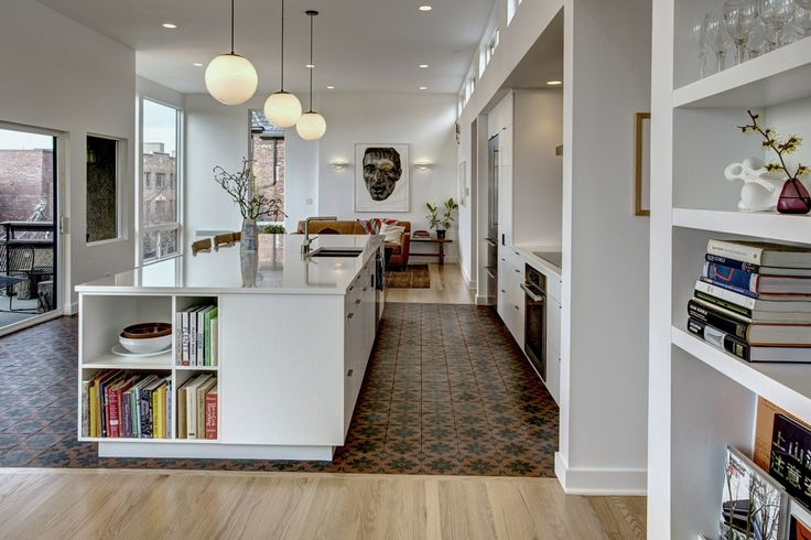 An earthy blanket of patterned concrete tile defines the kitchen and wraps up the cooktop/backsplash. Opposite, the massive island serves as a domestic hub, providing a generous gathering area for cooking, projects and entertaining.