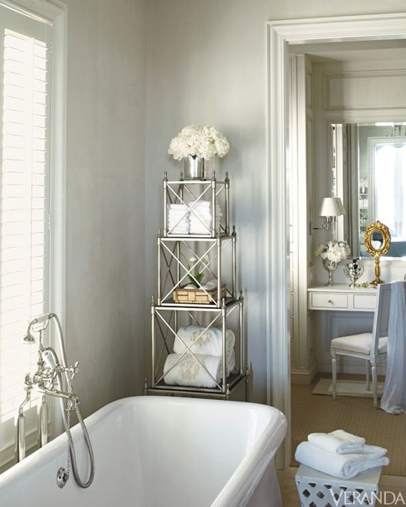 james michael howard gorgeous bathroom with pale gray walls and ivory moldings as well as soaking tub accented with floor mounted tub filler under window