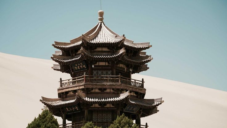 An intricately carved tower sits beside an oasis in the Gobi Desert.