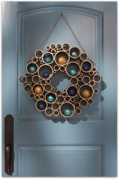 How-To: PVC Pipe Wreath Cut empty wrapping paper rolls, glue together, and spray paint before adding ornaments.
