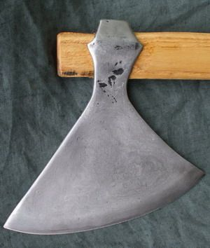 Thames Pattern Dane Axe 10th 11th Century. The head is then forged, the eye drifted out and it is ground and polished. Notice the dished effect into which the head is forged and ground leaving slightly hollow sides to reduce the weight - the edge appears as a ridge . The steel can be seen as a wavy line contrasting with the lighter coloured iron of the body. The head is mounted on an ash wood shaft.