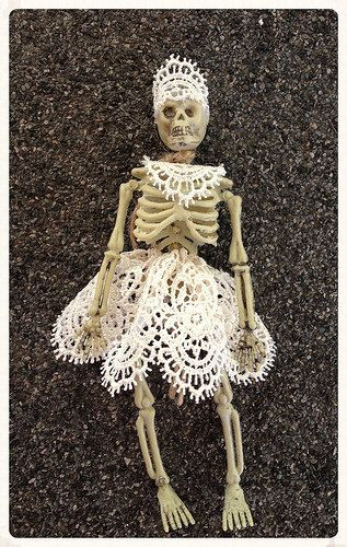 A six inch skeleton has a lace dress with a matching head piece.    can sit or hang