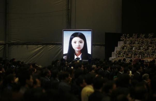 A portrait of a victim of sunken passenger ship Sewol, a student from Danwon High School, is displayed on a screen as mourners pay tribute at the official memorial altar for the victims in Ansan April 29, 2014. More than 300 people, most of them students and teachers from the Danwon High School, are dead or missing presumed dead after the April 16 disaster. The ferry sank on a routine trip from the port of Incheon, near Seoul, to the southern holiday island of Jeju. REUTERS/Kim Hong-Ji