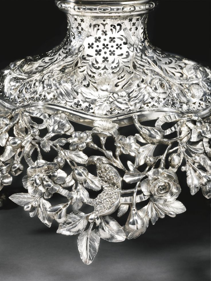 Detail A George III silver epergne, William Cripps, London, 1757 shaped oval, on four cast supports with detachable branches, the central section rising from a cast and pierced apron of ribbon-tied flower sprays and fruit, detachable basket, crested