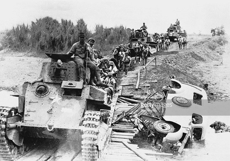 Japanese tanks are shown crossing a Burmese stream via a makeshift bridge during the early campaign against Burma. The overturned car is described in the original caption as a British Army vehicle. The Japanese tanks, according to observers, are poorly armored and lightly armed. This photo was obtained from an enemy source.