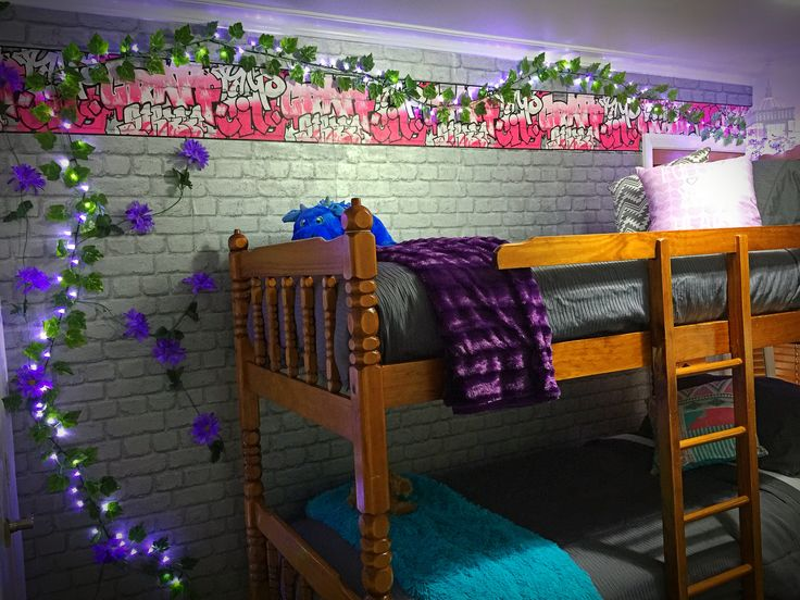 Brick wallpaper feature wall with graffiti border. Fake vines were from a discount store and purple flower vines were from a craft store (more expensive). Fairy lights on special from hardware store after Xmas. Hung lights and vines using 3M wall clips. Already had the beds and bought brand new bedding on special at Briscoes. Whole concept of an over-grown alley wall was my 9yr old daughter Beth's idea.