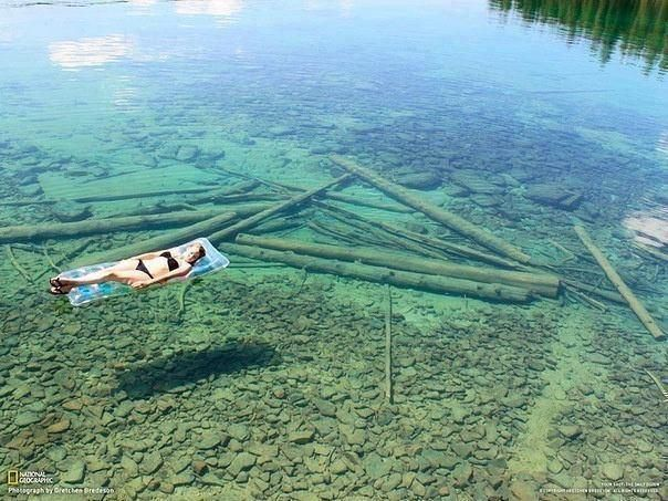 Because of the crystal-clear water, Flathead Lake in Montana seems shallow, but in reality is 371 feet in depth.  This woman is toward the shore.