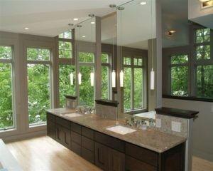 Dieses zeitgenössische Badezimmer-Design hat einen geräumigen Holzboden, grauen oberen Tabellenbereich, tiefe Waschbecken und vertikal spiegeln. / Foto: architektonische Immobilien durch Anders Inc