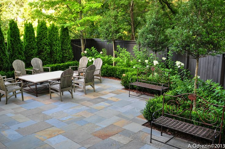 falkner gardens :: a pair of iron benches flank the terrace dining area in this Mountain Brook, Alabama residence