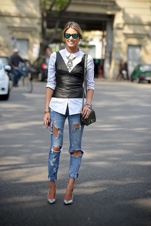 Девушка в рваных джинсах, белая рубашка и черный кожаный жилет