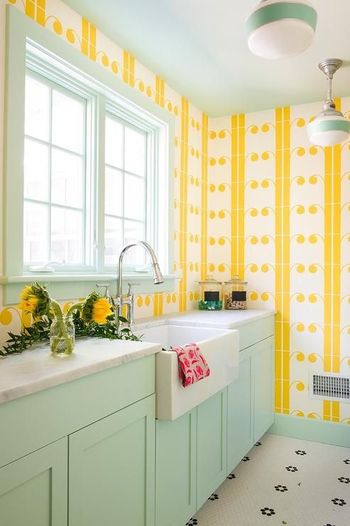 Vintage yellow and mint green laundry room features white and black vintage hex floor tiles complementing mint green cabinets topped with a honed Carrera marble countertop flanking a farmhouse sink finished with a polished nickel gooseneck faucet placed in front of a mint green framed window.