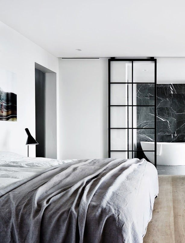 grey bedding + wood floors + vitrine + freestanding bath + black marble wall