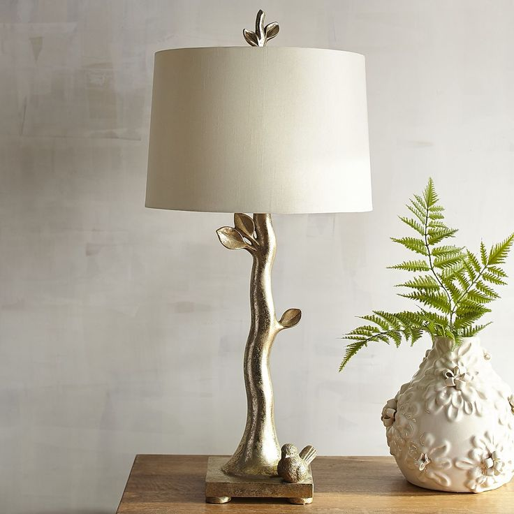 """The bird and branch theme has been around for ages, but by the looks of this metallic lamp, we've managed to make it modern. That's certainly a tall order—but given that this beauty measures 29"""" from bird at base to the twig finial atop its antique white shade—we think we delivered."""