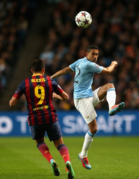 Gael Clichy of Manchester City clears under pressure from Alexis Sanchez of Barcelona during the UEFA Champions League Round of 16 first leg match between Manchester City and Barcelona at the Etihad Stadium on February 18, 2014 in Manchester, England.
