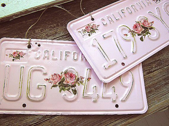 Back by popular demand! Restocked 2 more pink California license plates.  Genuine old California license plate painted shabby pink! Sanded for time-worn charm and detailed with large pink rose sprays. Ready to hang from attached twine. Holes for attachment to a bicycle or vehicle (for decoration only.)  This listing is for License Plate UG 3449. License Plate number 179 SYQ is available in a separate listing.  Measures approximately 12 x 6.