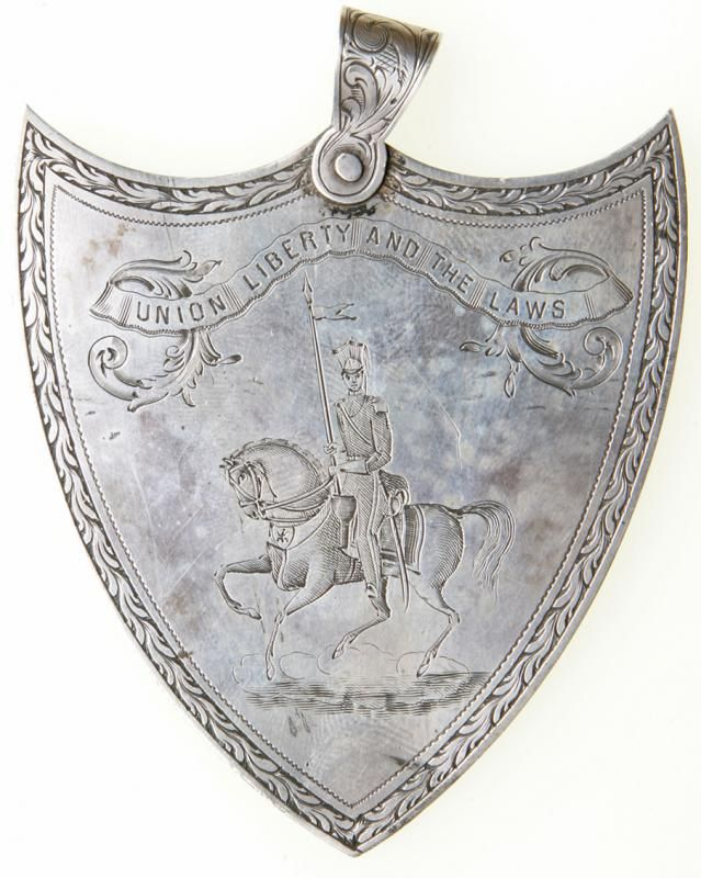 """1854 Boston Militia Unit """"National Lancers"""" Silver Shooting Medal Lancers were light cavalry that carried a nine-foot lance with a sharp finial designed to kill infantrymen. Lancers were the elite Polish and French cavalry who earned a reputation in Napoleon's army as shock troops. The National Lancers was formed in 1836 to serve as the city cavalry of Boston. The unit has remained active until today, without interruption, to this day, having served in the Civil War (Companies C & D 1st Mass. Cav.), as well as World Wars I & II. This 1.7 oz. medal is 2.5"""" x 2.75"""" high with scroll engraved suspension loop. The obverse displays a 3/8"""" wide chained border of acanthus leaves, with the central theme of a mounted lancer wearing the unit's distinctive uniform. Obverse: A scroll work riband at the top displays the unit's motto, """"Union Liberty and the Laws"""". Reverse An identical border with the legend """"National Lancers/ Awarded to/ for 2nd best Shot/ at Target practice/ September 20th/ 1854"""". An absolute stunning example with needle sharp details and fascinating engraving in the style of early 19th century. Extremely historic and worth a closer inspection to experience the extraordinary temperament it carries. Estimated Value $2,000 - 2,500. #Medals #MADonC"""