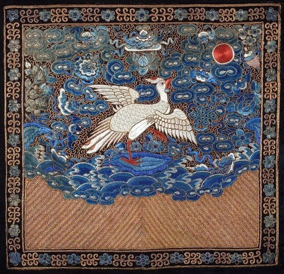 A mandarin square (rank badge) of a sixth rank civil servant, from the Qing Dynasty in the second half of the 19th century. Embroidery on silk, depicting an egret standing on a rock among waves.