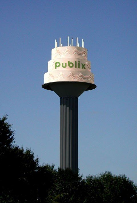 Publix Birthday Cake: Dedicated in 1982, the Hydro-cake stands 155 feet; holds 250,000 gallons. Its 8-foot candles weigh 250 lbs. each. Joe Blanton envisioned a water tower that was both functional and a landmark.