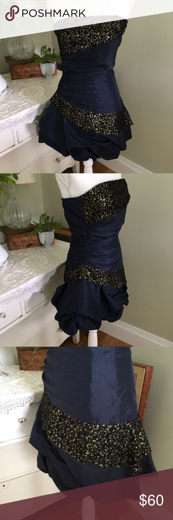 """Ya Los Angeles Blue Strapless Mini Formal Dress This satin style mini formal dress from Ya Los Angeles is youthful and fun. The form fitting strapless bodice showcases the flattering ruching detail while the short pick up skirt adds a playful touch. Side zipper and fully lined. 55% cotton; 45% polyester. Black and gold lace/sequins is frayed at edges (see 7th photo). Size: Small, but fits like an XXS or XS. Chest. 15.25"""". Waist: 13"""". Length (front): 27"""". Length (back): 23.5"""". Ya Los Angeles…"""