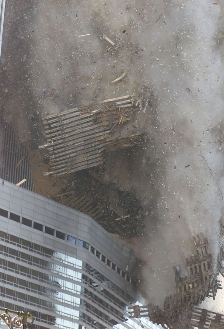 Debris rains down on the street as the South Tower of the World Trade Center collapses after hijacked planes crashed into the towers on September 11, 2001 in New York City