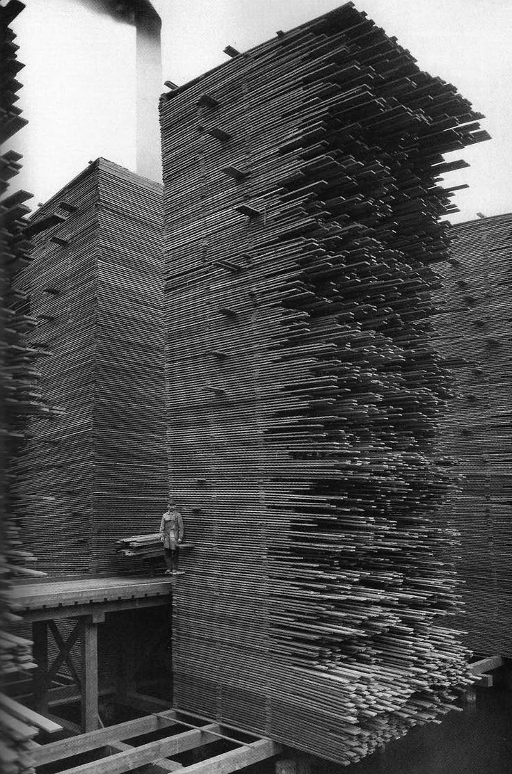 A man stands next the stacks of lumber at Cedar Mill, Seattle, 1919 ~ vintage everyday
