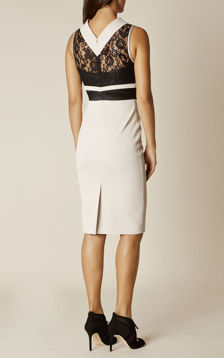 Кремовое платье-карандаш с цветочными кружевными деталями в районе плечей и спины, имеет черный пояс, который создает иллюзию будто платье состоит из  двух частей. Модель без рукавов с круглым вырезом и скрытой застежкой-молнией по центру спины.
