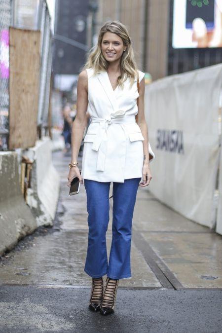 Kobieta ubrana w białą kamizelkę, niebieskie jeansy typu dzwony i wiązane, czarne szpilki.