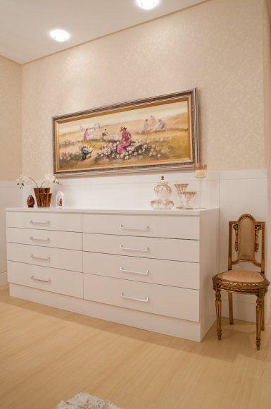 Na suíte do casal, por solicitação da cliente, uma grande cômoda foi disposta para oferecer apoio ao closet. Ao lado, a cadeira em dourado envelhecido que pertence à moradora desde a sua juventude.