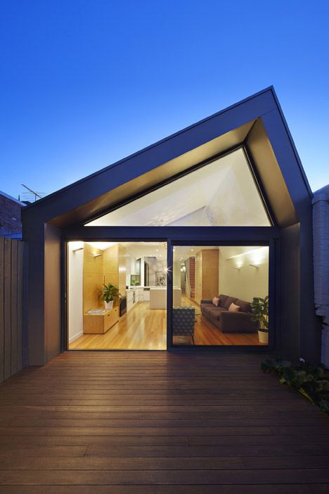 A pair of steel-clad volumes with pitched roofs and glazed gables provide additional living space behind the ornamental facade of this Victorian terrace in Melbourne.