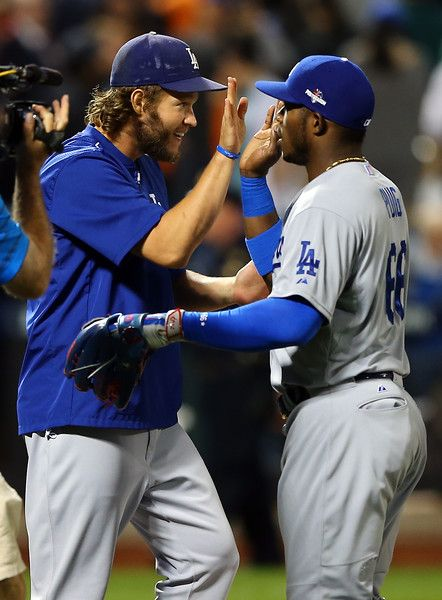 Clayton Kershaw #22 and Yasiel Puig #66 of the Los Angeles Dodgers celebrate after defeating the New York Mets in game four of the National League Division Series at Citi Field on October 13, 2015 in New York City.  The Dodgers defeated the Mets with a score of 3 to 1.  (Photo by Elsa/Getty Images)