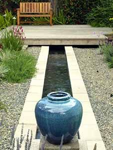 The homeowners simply sandwiched pond liner between layers of cinder block, layered the bottom of the rill with river stones and filled it with water. A large urn creates a focal point on one end and the rill disappears beneath the deck.