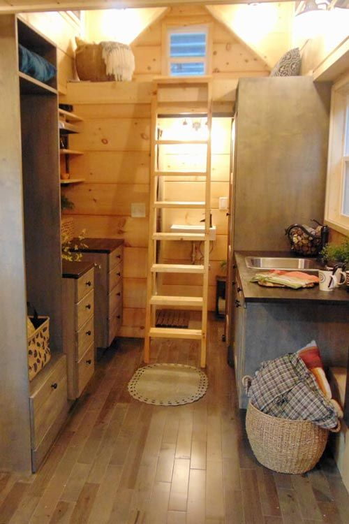 """Inside this tiny house is custom oak flooring with a grey stain, 1""""x12"""" tongue and groove white pine on the walls, and 1""""x8"""" pine on the ceiling."""
