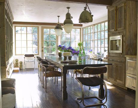Clad in wood from a tobacco shed, this L.A. kitchen combines a rustic look with salvaged finds, like the vintage chrome chairs that are upholstered in Brazilian cowhide. Homeowners Robbin and Hillary Hayne even chose not to match the vintage pendant lights.