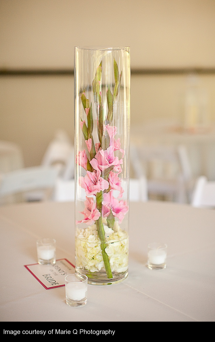 very simple in a narrow cylinder vase with hydrangea puff in the bottom