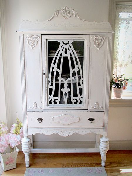 This antique china cabinet is a favorite memory of grandmom's cottage home. The breakfront with all its beautiful embellishments has been refinished a linen white and lightly distressed. A hint of pink peeks through in the applique on the bottom drawer. The cabinet features original hardware and a fancy design fretwork behind the glass door.... View Article