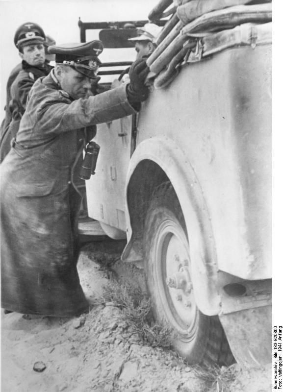 Colonel General Erwin Rommel and General Siegfried Westphal helping with pushing a stuck vehicle, North Africa, early 1941.