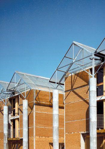 """Gilles perraudin Maisons en pisé, L'isle d'abeau (1981-1985) S'agissant de mettre en œuvre un matériau oublié, la terre, le parti sur la forme générale de la maison reste simple. S'inspirant des maisons traditionnelles les espaces d'habitation se prolongent sur l'extérieur par l'intermédiaire   d'espaces """"saisonniers"""" (véranda, terrasse, balcon) qui, protégés par des treilles ou des murs écrans, forment de véritables espaces habitables quand les conditions climatiques sont favorables."""