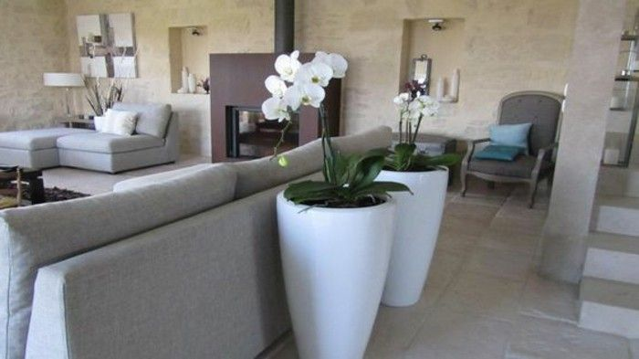 big ceramic vases in white, with planted white orchids, near light gray sofa, living room color ideas, spotty pale beige walls, dark brown fireplace