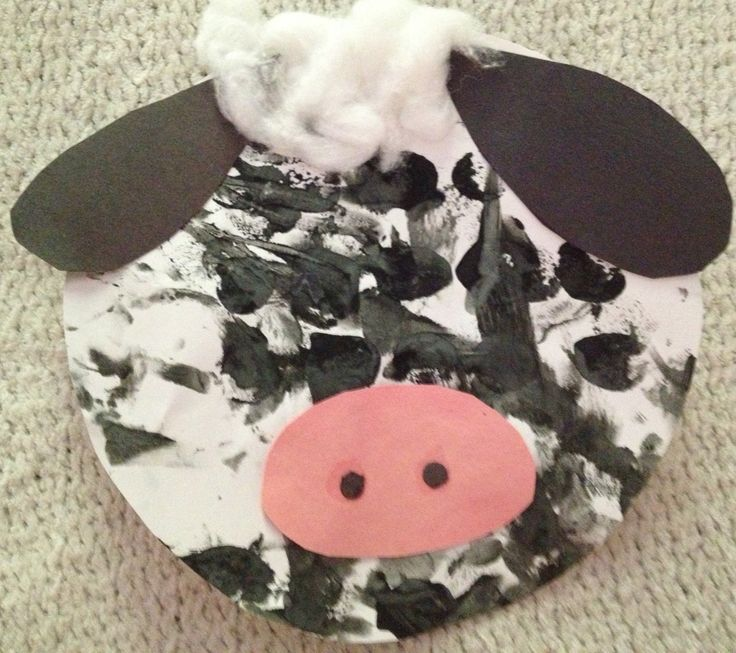 A  toddler creates a black lamb with the help of his teacher. The student paints the plate and then the teacher helps assemble the keepsake to take home.