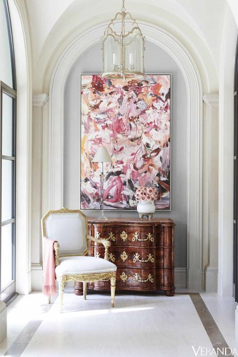 Choice antiques and eye-catching art make a visual statement outside the master bedroom.