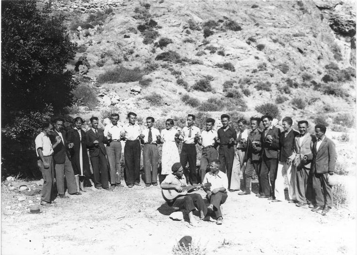 Η ζωή στην Ανάφη μέσα από τον φωτογραφικό φακό των εξορίστων στο νησί Φωτογραφία στην ύπαιθρο. Αριστερά της εικόνας υπάρχει μια χαρουπιά και έτσι έχει εντοπιστεί το μέρος, η περιοχή Καλίστα, κοντά στις Μηλιές. Χορεύουν δεκαεπτά άτομα, ενώ δυο στη σειρά των χορευτών είναι γυναίκες.(1938)